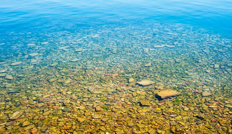 Água pouco profunda transparente com parte inferior rochosa imagem de stock