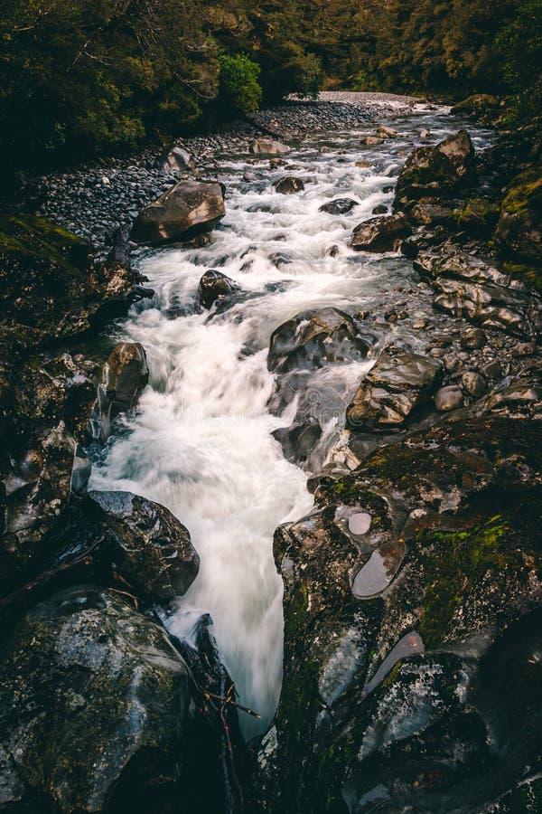 Água que corre através do córrego sobre rochas escuras da queda da água imagens de stock royalty free