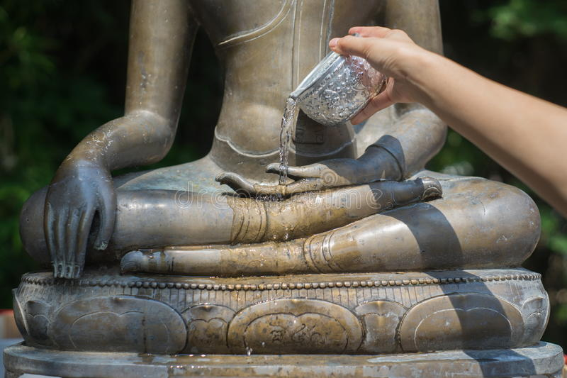 Água que derrama à estátua de Buddha imagem de stock