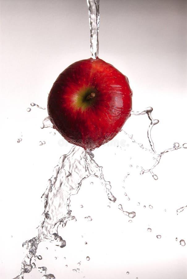 Água que derrama fora da maçã vermelha. imagem de stock