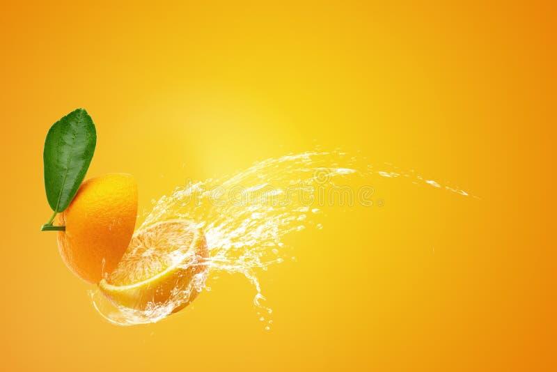 Água que espirra em laranjas cortadas frescas do ‹do †do ‹do †e no fruto alaranjado no fundo alaranjado imagem de stock