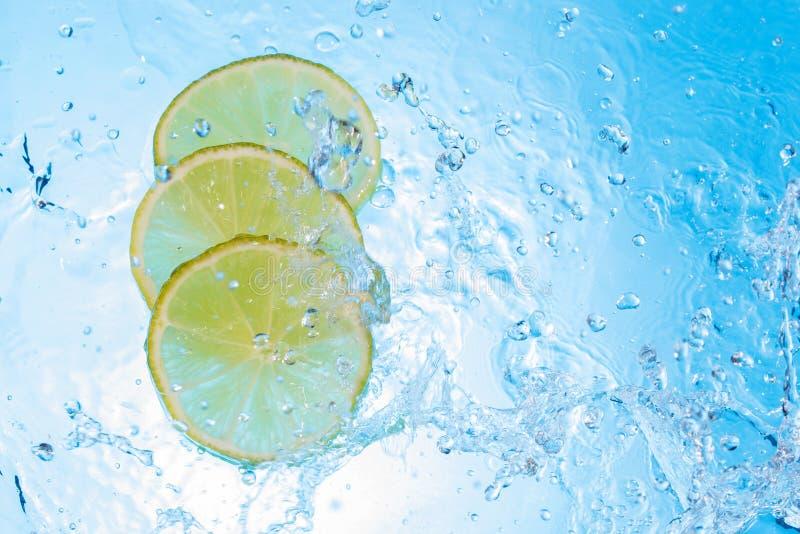 Água que está sendo derramada dentro algumas fatias do limão fotos de stock royalty free