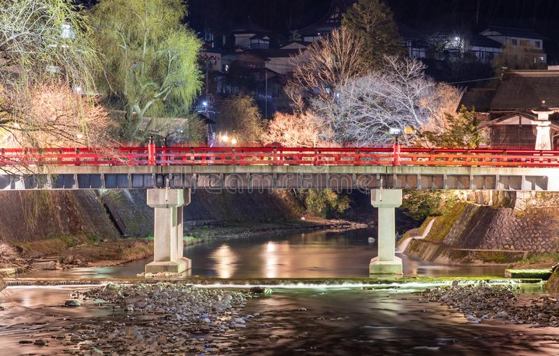 Água que flui abaixo de uma ponte vermelha na noite foto de stock