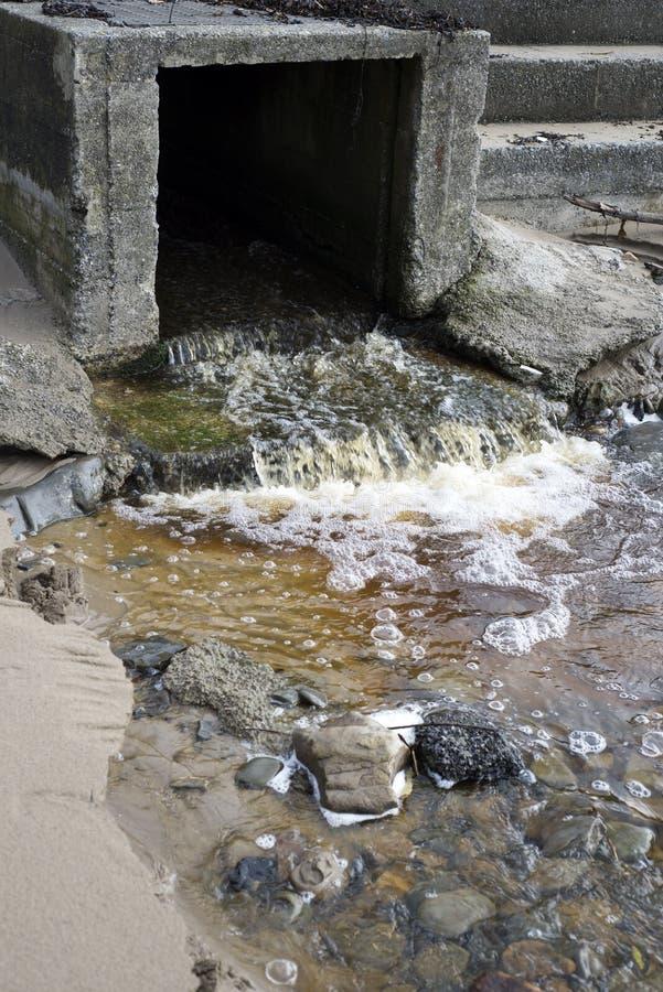 Água que flui de um dreno da tempestade fotografia de stock