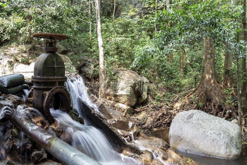 A água que flui do dreno de aço para o riacho da cascata na floresta tropical imagens de stock