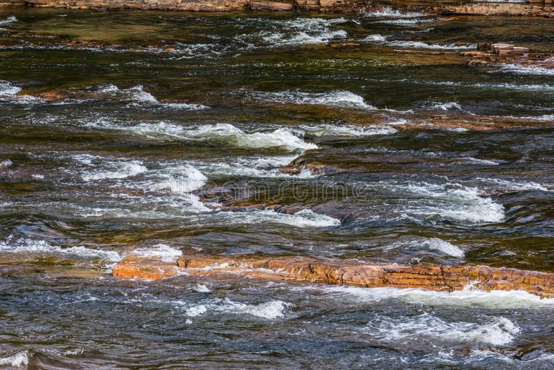 Água que flui sobre as rochas que formam pouco rapidsl imagens de stock royalty free