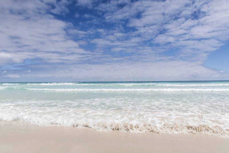 Água que lava acima na areia branca com uma vista de uma ilha; Galão fotos de stock royalty free