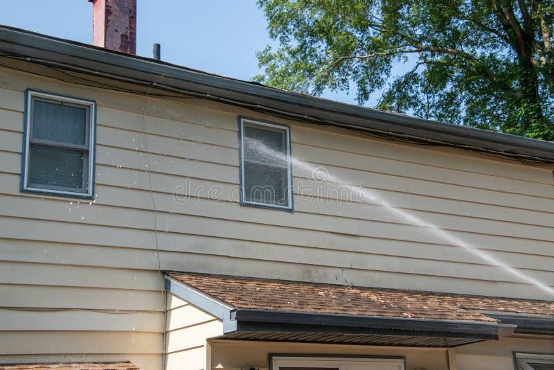 A água que pulveriza no tapume de uma casa como o bocado sendo poder está sendo lavada em um dia ensolarado foto de stock royalty free