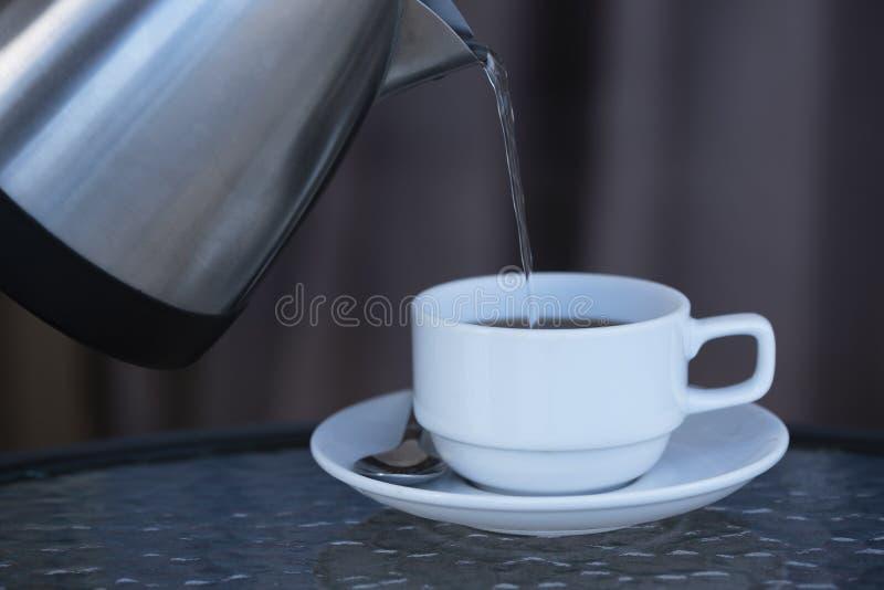 Água quente de derramamento que faz o café quente foto de stock