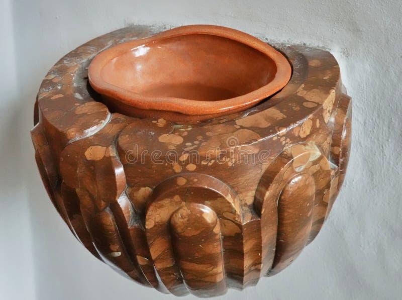 Água sagrada feita de mármore com um remanescente de água consagrado pelo padre imagens de stock royalty free