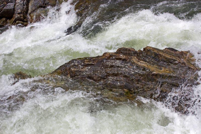 Água turbulenta clara na cama rochosa do córrego da montanha imagens de stock