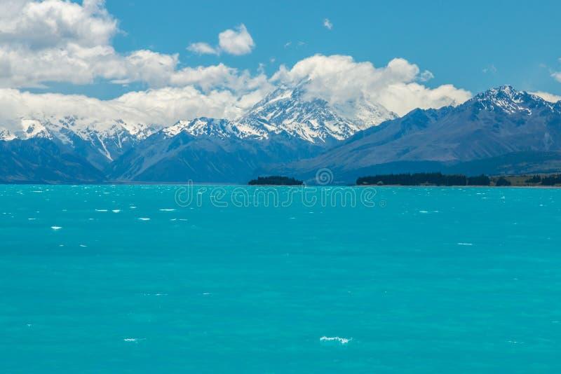 Águas azuis brilhantes do lago Pukaki, uma atração turística principal na ilha sul do ` s de Nova Zelândia imagem de stock