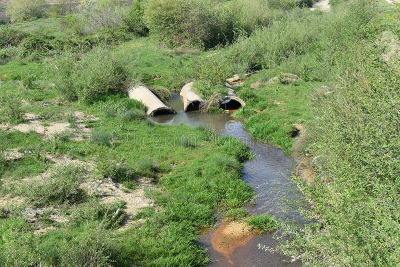 Águas residuais enegrecidas das plantas industriais e das lagoas do desperdício que fluem da extremidade do encanamento aos nasce imagem de stock