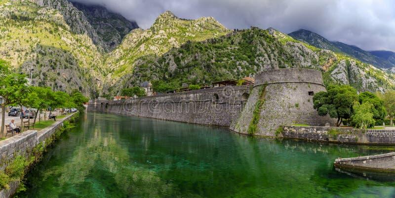 Águas verdes esmeraldas da baía de Kotor ou do Boka Kotorska e a parede antiga da antiga fortaleza Venetian de Kotor em Montenegr fotografia de stock