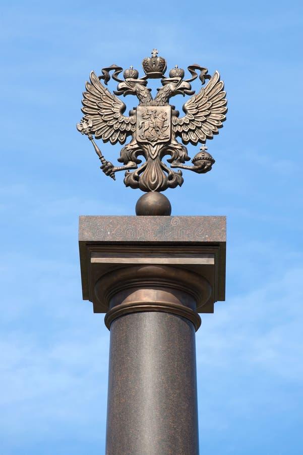 águia Dois-dirigida do russo sobre uma coluna contra um céu azul Fragmento do monumento da glória militar fotos de stock royalty free