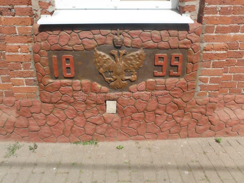 A águia dois-dirigida na parede da construção em 1899, uma raridade fotografia de stock royalty free