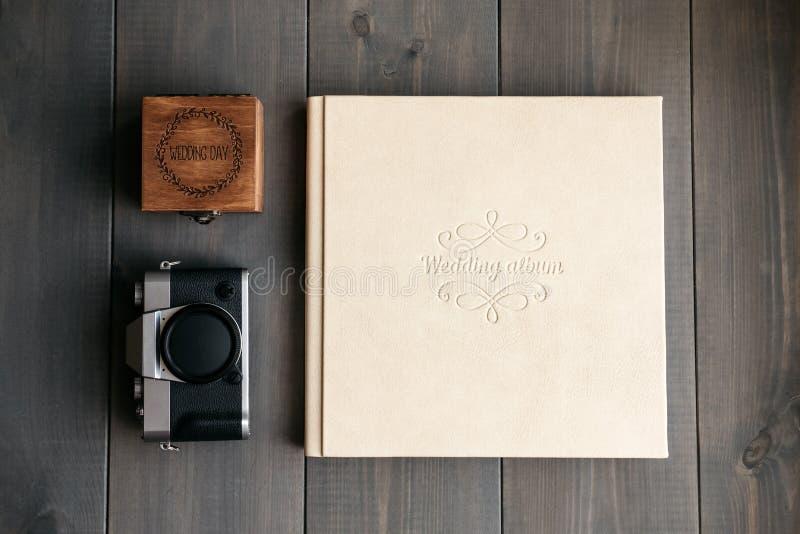 Álbum do casamento do couro branco, caixa de madeira com dia do casamento da inscrição e câmera da foto do vintage imagem de stock