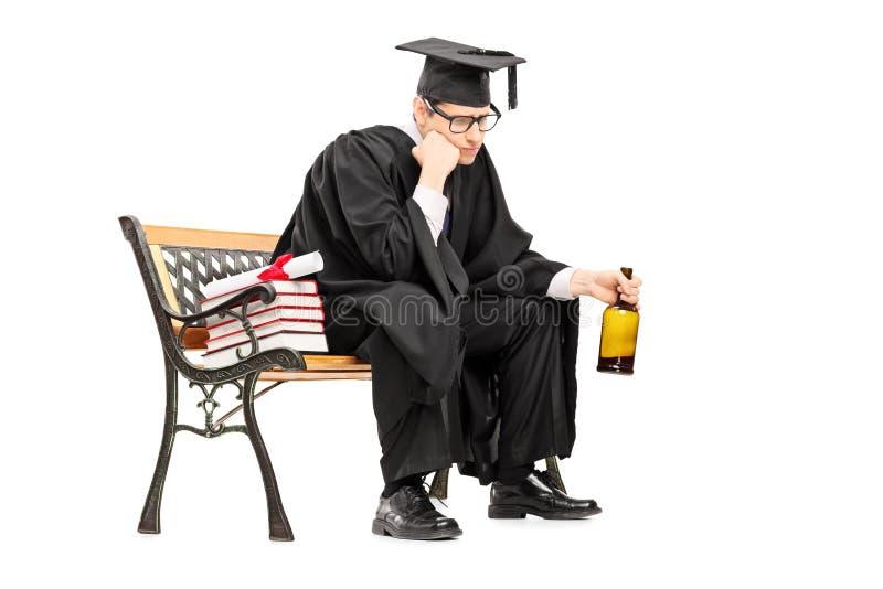 Álcool bebendo triste do graduado de faculdade assentado no banco imagem de stock royalty free