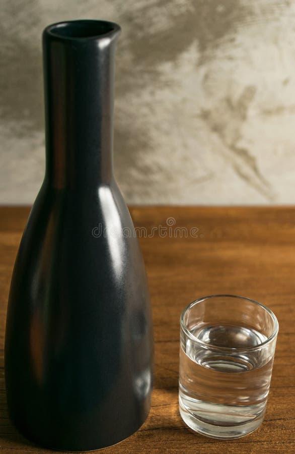 Álcool, uísque japannese, causa na madeira da tabela na frente do concre imagens de stock royalty free
