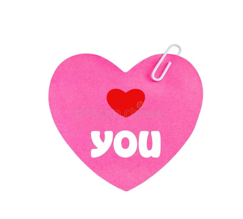 Ámele mensaje en el papel del rosa de la forma del corazón foto de archivo