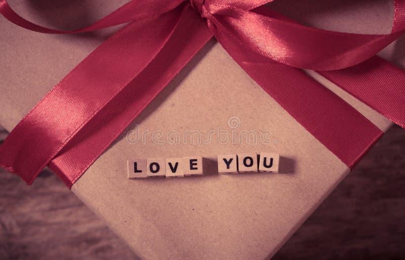 Ámele mensaje escrito con los cubos de madera en el presente del regalo del amor para día de San Valentín y el aniversario foto de archivo libre de regalías