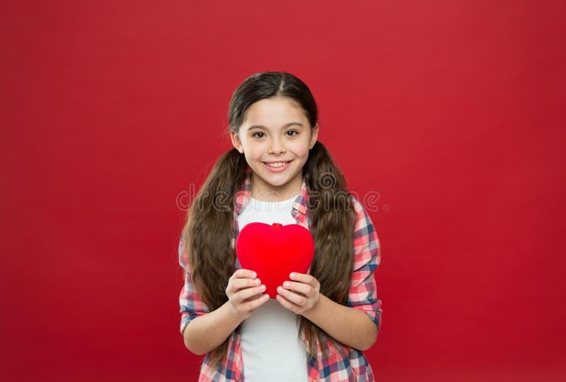 Ámele solamente en mi corazón por siempre jamás Poco niño que expresa amor en día de San Valentín Muchacha linda en amor teniendo imagen de archivo