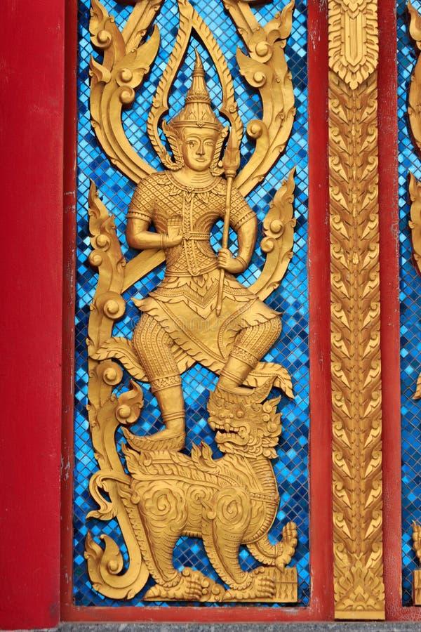 Ángel anhelado de oro en el templo tailandés Windows foto de archivo libre de regalías