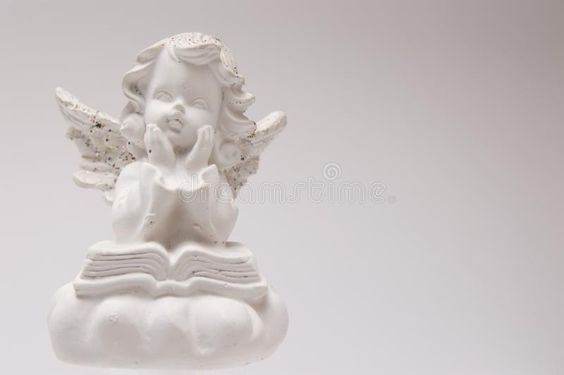 Ángel blanco del yeso en una lectura de fondo blanca un libro y un pensamiento fotos de archivo libres de regalías