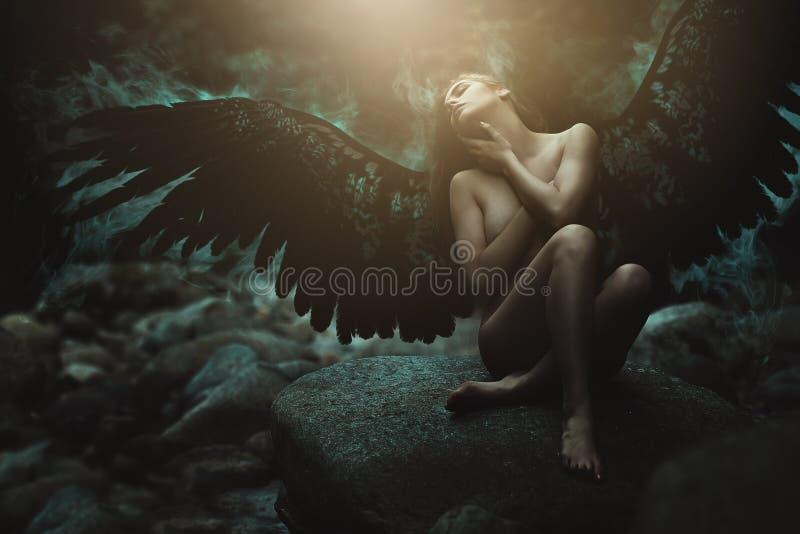 Ángel caido con las alas negras imagenes de archivo