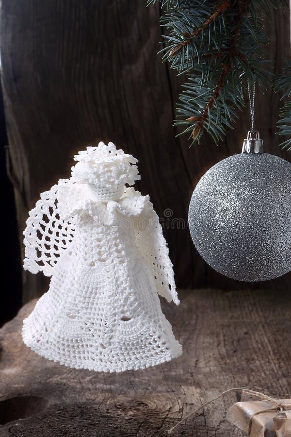 Ángel de la Navidad con una bola en el árbol de navidad imagenes de archivo