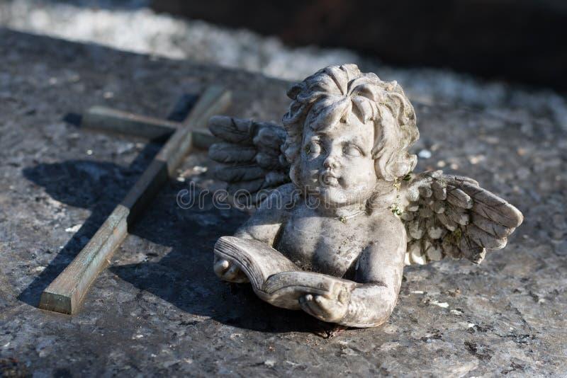 Ángel delante de una cruz - lectura de un libro fotos de archivo