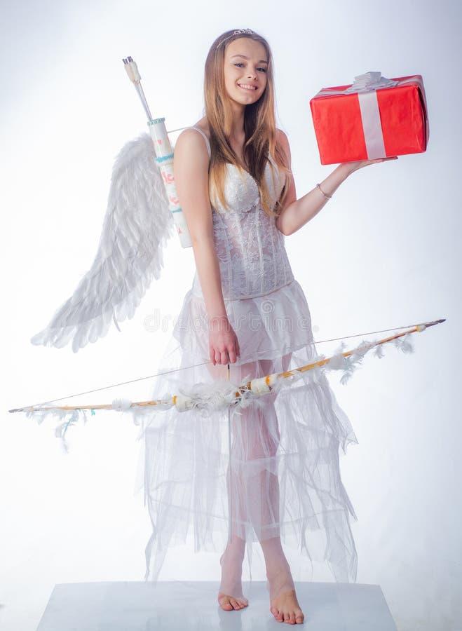 Ángel en el actual regalo del amor Muchacha inocente con las alas del ángel que se oponen con el arco y la flecha al fondo blanco fotografía de archivo