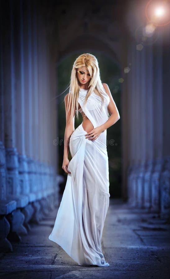Ángel rubio hermoso con las alas de la luz blanca y la presentación blanca del velo al aire libre fotografía de archivo libre de regalías