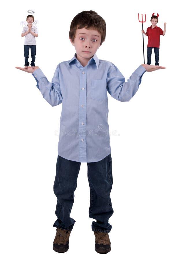Ángel y diablo en un muchacho joven fotografía de archivo