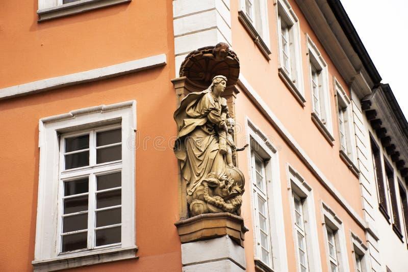 Ángel y estatua del sacerdote en el frente del edificio retro clásico imagen de archivo libre de regalías