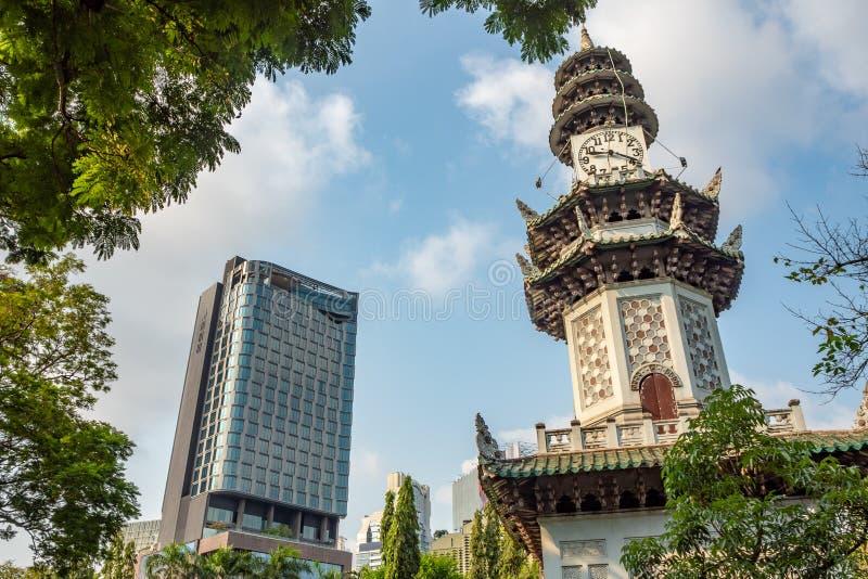 Ángulo bajo de la torre de reloj hermosa en parque con primero plano verde de la hoja y el edificio con el fondo del cielo azul imagen de archivo