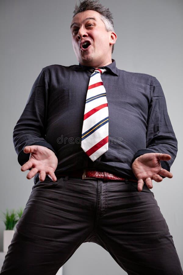 Ángulo bajo de las rodillas para arriba de un hombre que canta fotografía de archivo libre de regalías