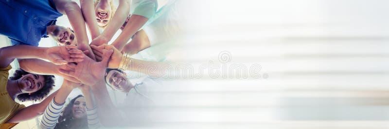 Ángulo bajo del equipo y el juntar de las manos creativas y de la transición blanca borrosa fotografía de archivo