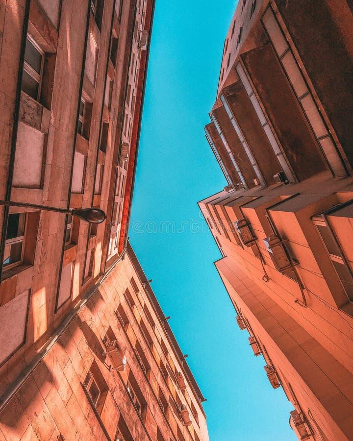 Ángulo bajo vertical tirado de edificios concretos marrones fotografía de archivo