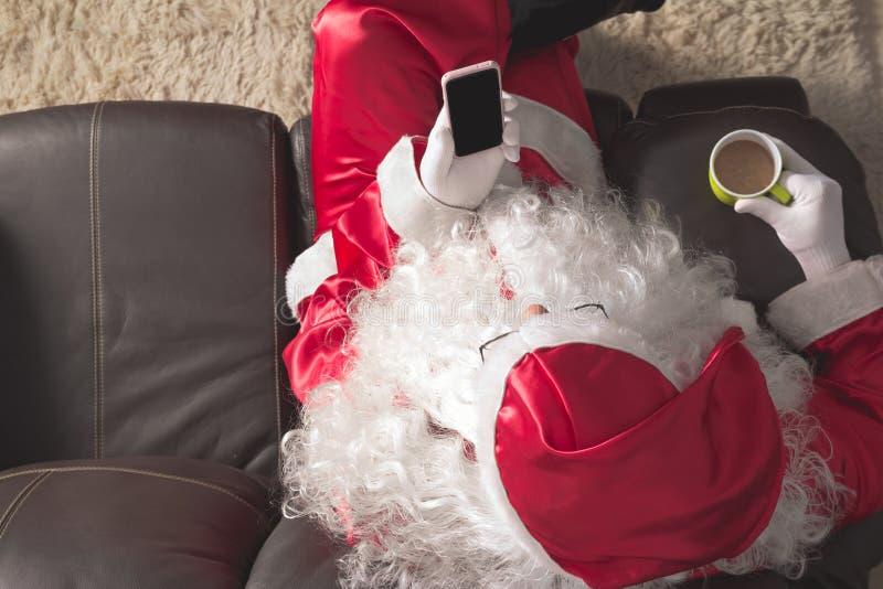 Ángulo de arriba hacia abajo de Santa Claus que se sienta en el sofá en casa que sostiene el ce foto de archivo