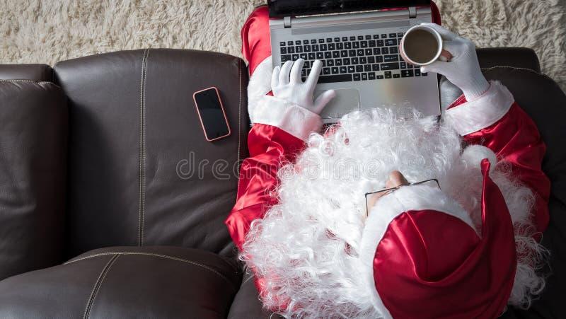 Ángulo de arriba hacia abajo de Santa Claus que se sienta en sofá en casa usando el alambre fotos de archivo