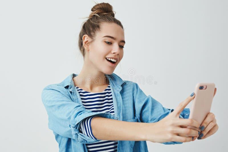 Ángulo del hallazgo de la muchacha tomar el selfie impresionante para fijar Internet en línea Mujer de moda elegante atractiva  foto de archivo libre de regalías