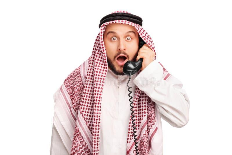 Árabe novo surpreendido que fala no telefone fotografia de stock royalty free