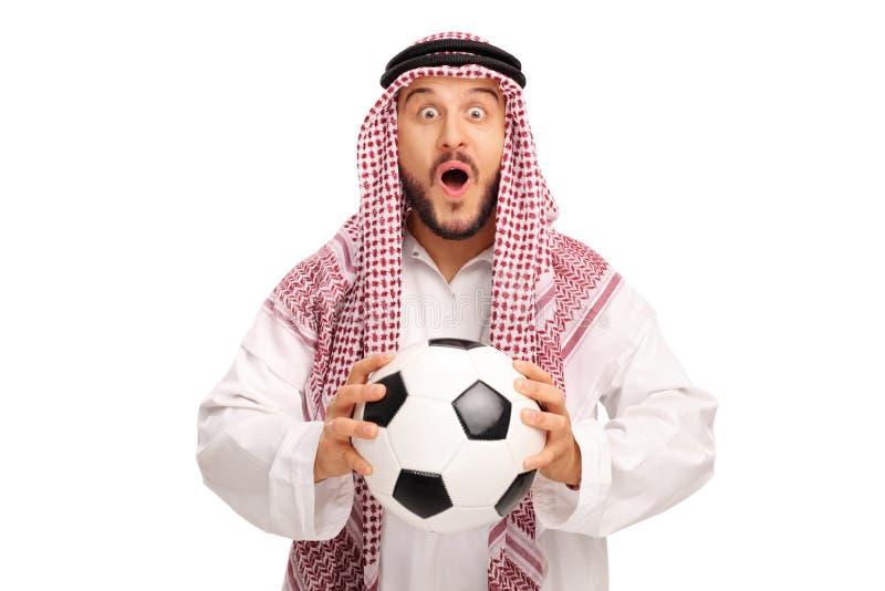 Árabe novo surpreendido que guarda um futebol fotografia de stock