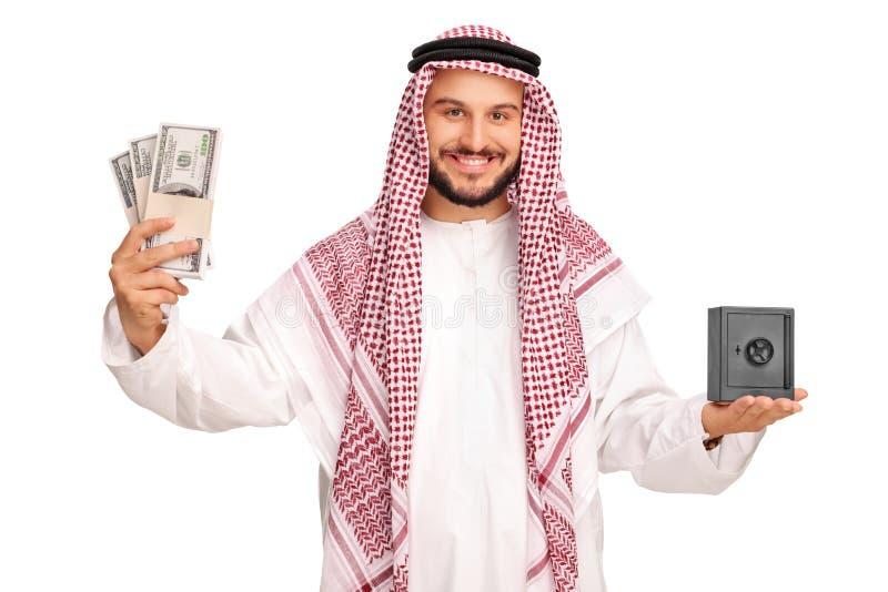 Árabe que sostiene el dinero y una pequeña caja fuerte del metal foto de archivo