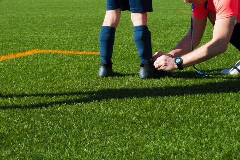 Árbitro adulto que amarra uma sapata a um jogador de futebol da criança imagem de stock royalty free