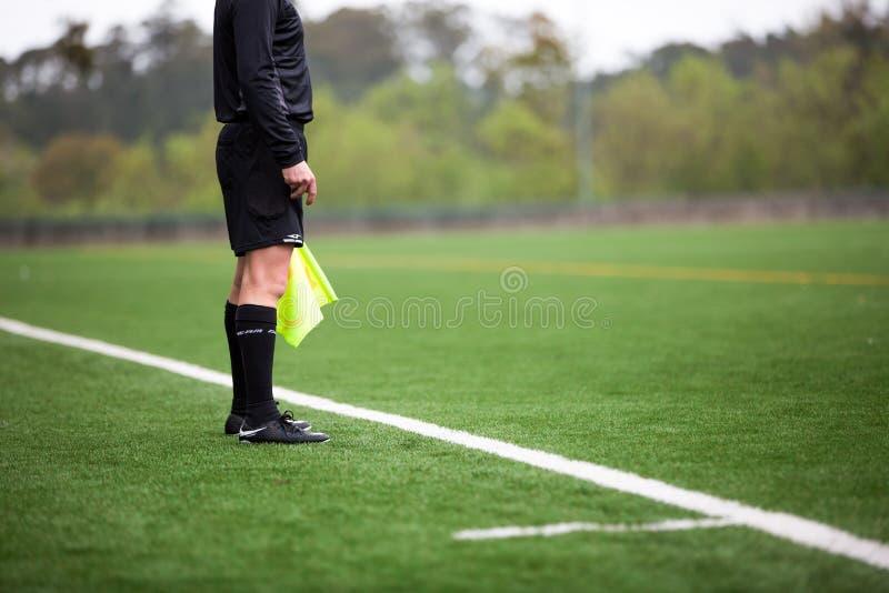 Árbitro del fútbol o del fútbol que se coloca en campo de hierba artificial verde foto de archivo