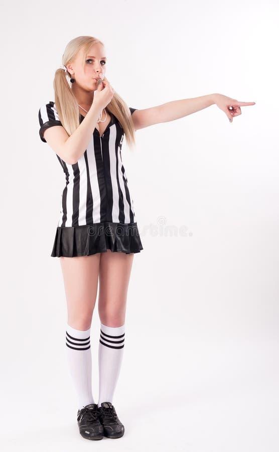 Árbitro do futebol que assobia e que aponta ao lado imagem de stock