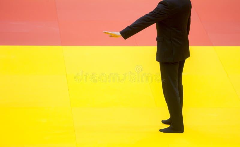 Árbitro en una alfombra de lucha amarilla en el gimnasio fotos de archivo