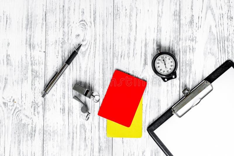 Árbitro que prepara-se à competição Cartões amarelos e vermelhos, cronômetro, assobio na opinião superior do fundo de madeira imagem de stock royalty free